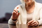 částečný pohled starší ženy držící pilulku, selektivní zaměření