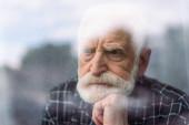 truchlící starší muž odvrací pohled okenním sklem, zatímco drží ruku u brady