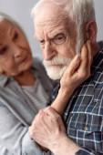 starší žena dotýkající se tváře manžela trpícího demencí