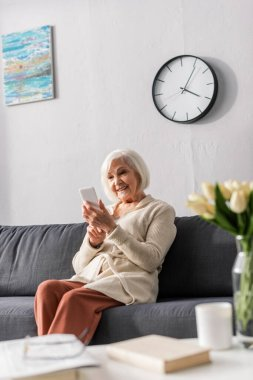 Selective focus of happy senior woman using smartphone while sitting on sofa stock vector