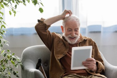 cheerful senior man touching had while using digital tablet in armchair