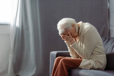 depressed senior woman sitting on sofa with bowed had and obscuring face with hands