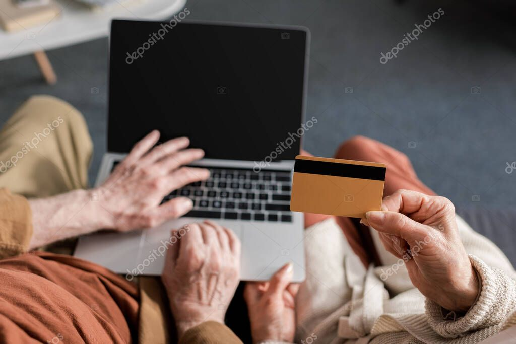 Cropped view of senior man using aptop with blank screen near wife holding credit card, top view stock vector