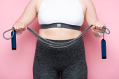 Photo partial view of overweight girl in sportswear holding jumping rope on pink