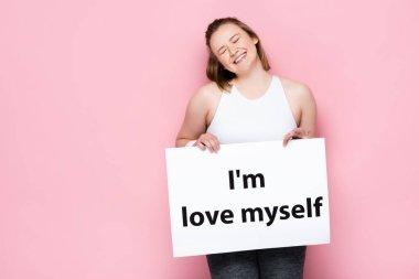 cheerful overweight girl with closed eyes holding placard with I love myself inscription on pink