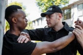 Photo policeman in uniform detaining african american man on street, racism concept