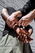 nízký úhel pohledu policista dotýká spoutaný africký Američan muž