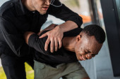Photo angry police officer detaining african american man suffering from pain, racism concept
