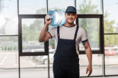 Photo cheerful delivery man in cap and uniform holding gallon of water in bottle