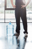 Photo cropped view of delivery man in uniform standing with hands on hips near bottled water