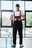Photo cheerful delivery man in uniform showing thumbs up near gallon of bottled water