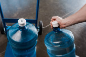 Photo cropped view of delivery man touching bottle with water near hand truck