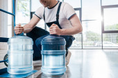 Photo cropped view of happy delivery man holding blue bottles with water near hand truck