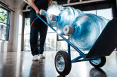 Photo cropped view of delivery man in uniform holding hand truck with purified water in bottles