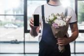 vágott kilátás a szállító férfi gazdaság csokor virágzó virágok és okostelefon üres képernyőn