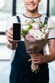 oříznutý pohled na šťastný doručovatel drží kytice kvetoucích květin a smartphone s prázdnou obrazovkou