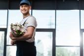 šťastný donáška muž v čepici a uniformu drží kytice kvetoucích květin