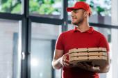 šťastný doručovatel v čepici dívá pryč a drží krabice od pizzy