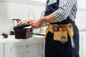 Photo Cropped view of plumber in overalls opening toolbox on worktop in kitchen