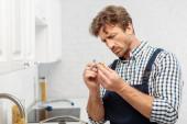 Hezký instalatér drží rukojeť kohoutku v kuchyni