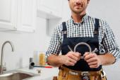 Ausgeschnittene Ansicht des Klempners in Arbeitskleidung und Werkzeuggürtel mit Metallrohr in der Küche
