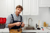 Photo Plumber holding metal pipe and wrench while working in kitchen