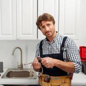 Handsome Klempner hält Metallrohr und Schraubenschlüssel in Küche
