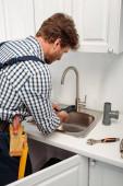 Fotografie Klempner mit Rohrschlüssel beim Befestigen von Wasserhähnen in der Nähe von Kunststoffrohren auf der Arbeitsplatte in der Küche
