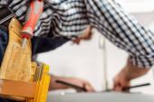 Selektivní zaměření instalatéra v nástrojovém pásu pracující v kuchyni