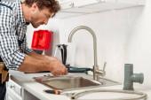 Boční pohled pohledný opravář pomocí trubkového klíče při opravě kuchyňského kohoutku