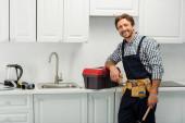 Lächelnder Installateur blickt in Kamera, während er Kolben in der Nähe des Werkzeugkastens auf der Arbeitsplatte in der Küche hält