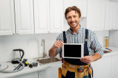 Photo Smiling workman holding digital tablet with blank screen near tools on kitchen worktop