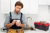 Pensive instalatér pomocí smartphonu v blízkosti nářadí a dřez v kuchyni