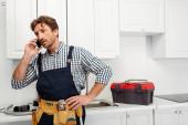 Instalatér v pracovním a nástrojovém pásu mluví na smartphonu u nářadí na pracovní desce v kuchyni