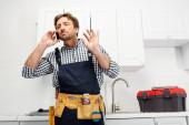 Schöner Klempner in Overalls und Werkzeuggürtel, der in der Küche mit dem Smartphone spricht