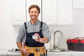 Lächelnder Klempner in Arbeitskleidung mit leerer Karte und Blick in die Kamera in der Küche