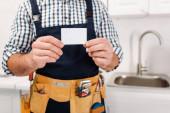 Oříznutý pohled na dělníka v opasku s nářadím s prázdnou kartou v kuchyni