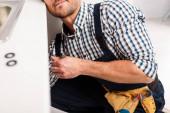 Ausgeschnittene Ansicht des Klempners, der Metallrohr hält, während er Spüle in Küche repariert