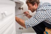 Boční pohled na instalatéra držícího kovovou trubku při upevňování kuchyňského dřezu