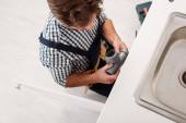 Ansicht des Installateurs, der Kunststoffrohr hält, während er Spüle in Küche fixiert