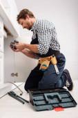 Selektiver Fokus des hübschen Klempners, der Kunststoffrohr in der Nähe von Schraubenschlüssel und Werkzeugkiste auf dem Boden in der Küche hält