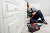 Selektiver Fokus des Klempners, der den Schraubenschlüssel hält, während er die Küchenspüle in der Nähe von Werkzeugen und Werkzeugkiste auf dem Boden repariert