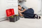 Fotografie Klempner schläft auf dem Boden in der Nähe von Werkzeugkasten und Waschbecken in der Küche