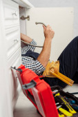 Selektiver Fokus des Arbeiters, der Metallrohr in der Nähe des offenen Werkzeugkastens hält, während er die Küchenspüle fixiert