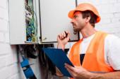 Selektivní zaměření pohledného elektrikáře v bezpečnostní vestě a hardhat držení pera a schránky při pohledu na elektrický panel
