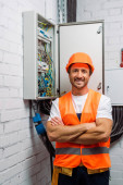 Handsome electrician in hardhat and safety vest smiling at camera near electrical distribution box