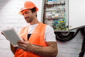 Selective focus of handsome electrician using digital tablet near electrical distribution box