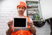 Selektivní zaměření pohledného elektrikáře zobrazující digitální tablet s prázdnou obrazovkou v blízkosti elektrické skříňky