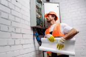 Hezký elektrikář držící plán u rozvodné skříně