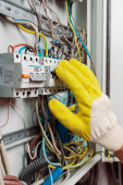 Cropped view of electrician in glove including toggle switches of electric panel